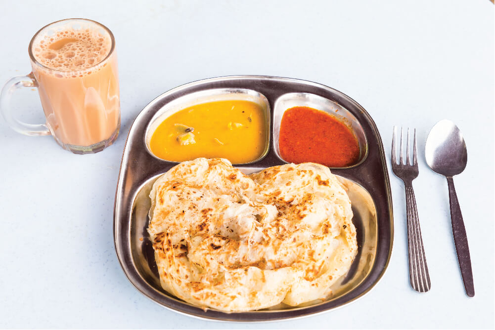 roti canai and teh tarik served hot on a table