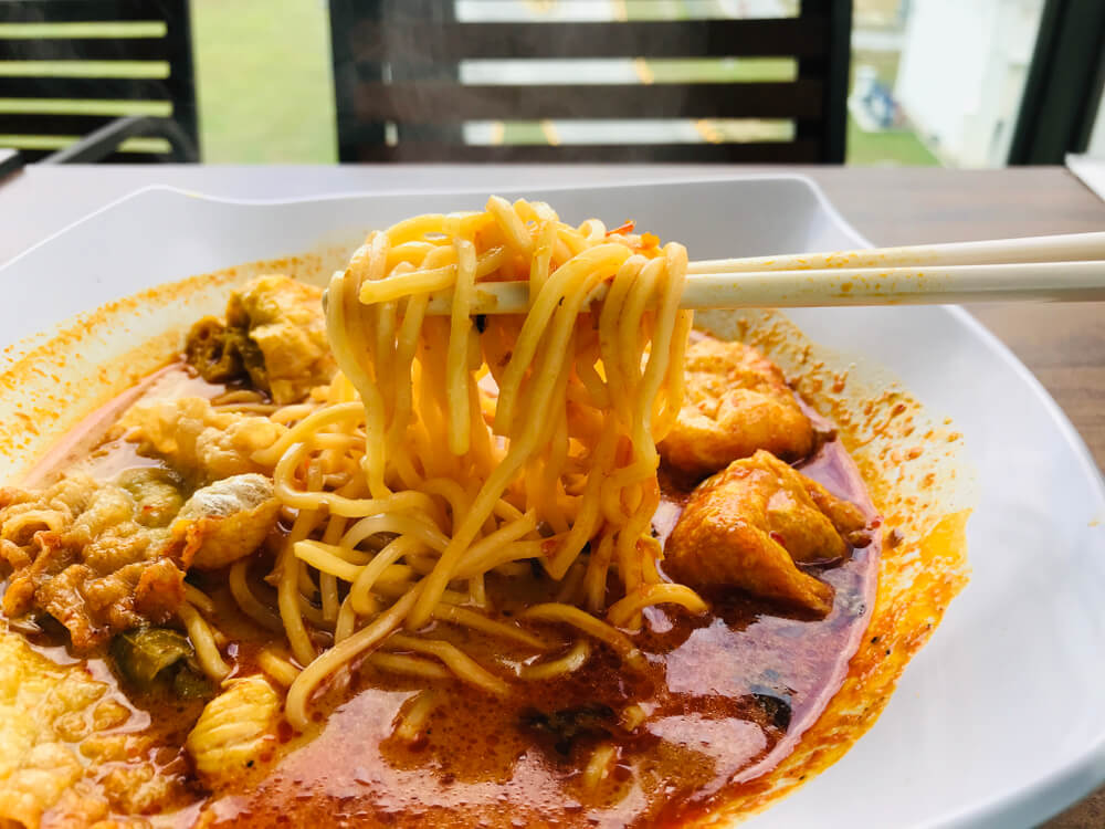 Eating curry mee with chopstick