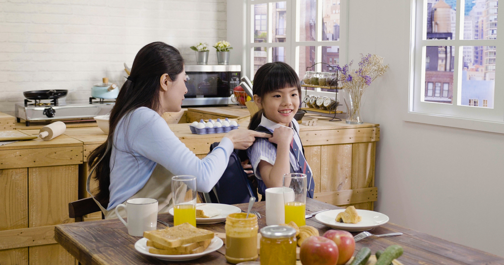 Mother packing healthy food for daughter