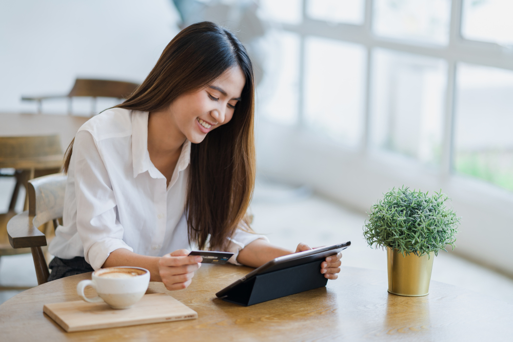Young attractive happy Asian woman is using tablet for shopping and paying online by debit or credit cards