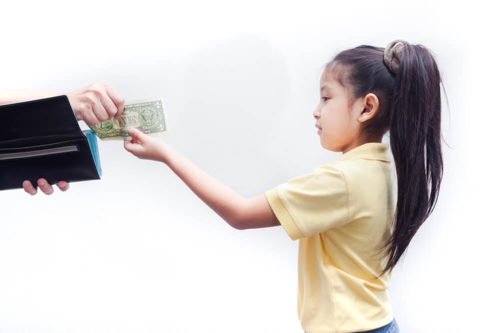 Girl receiving allowance from parent