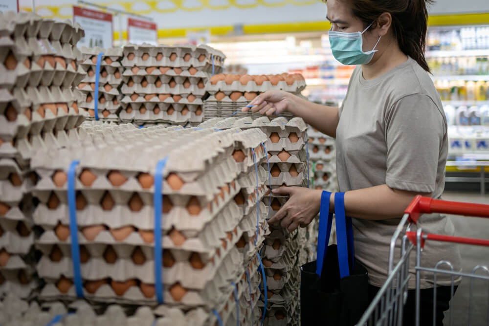 Asian woman buying eggs at the store
