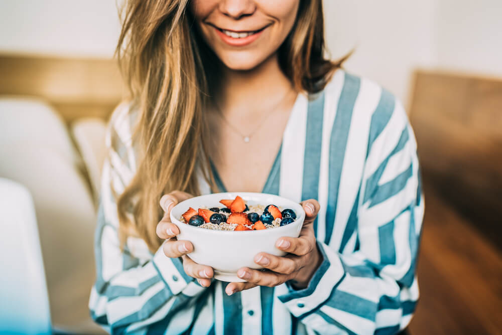 Happy woman having a bowl of oats and fruits in her pyjamas