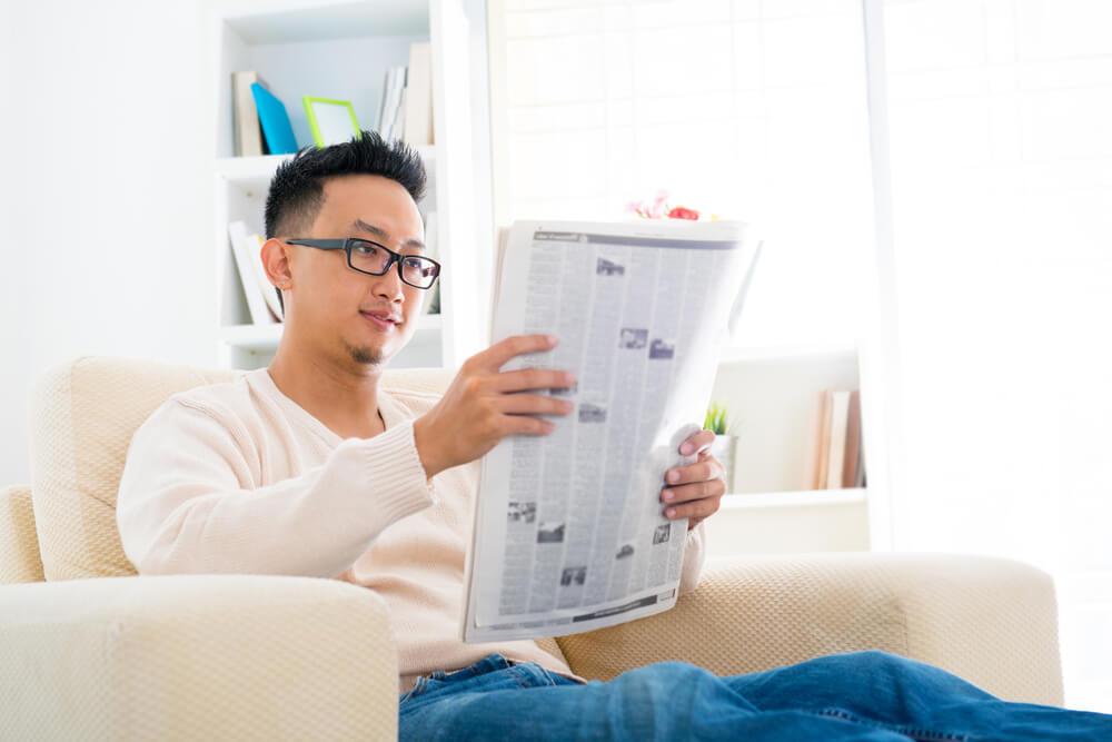 Millennial man reading the newspaper.