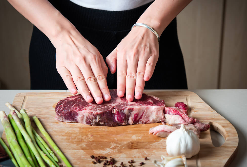 Woman pressing down a meat