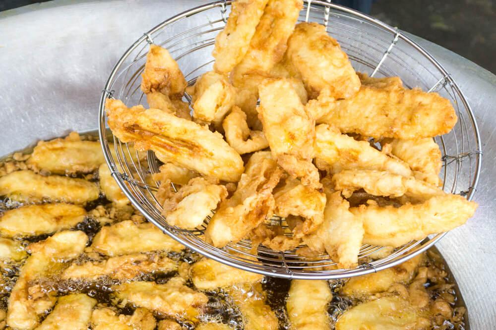 Crunchy pisang goreng being fried in a big wok