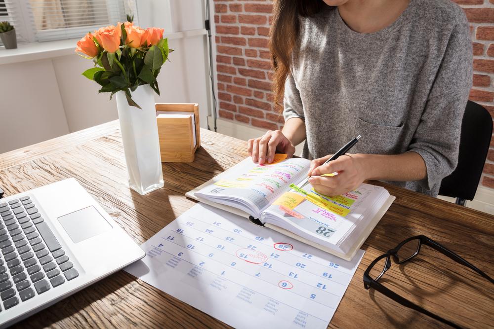 Woman marking dates on her calendar