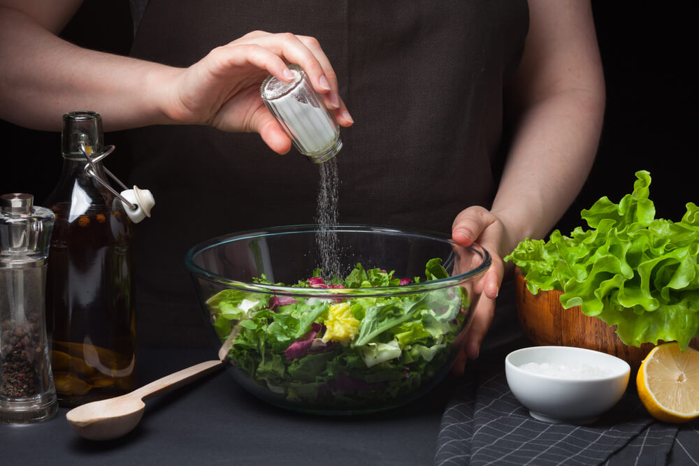 Person adding salt into a bowl of salad