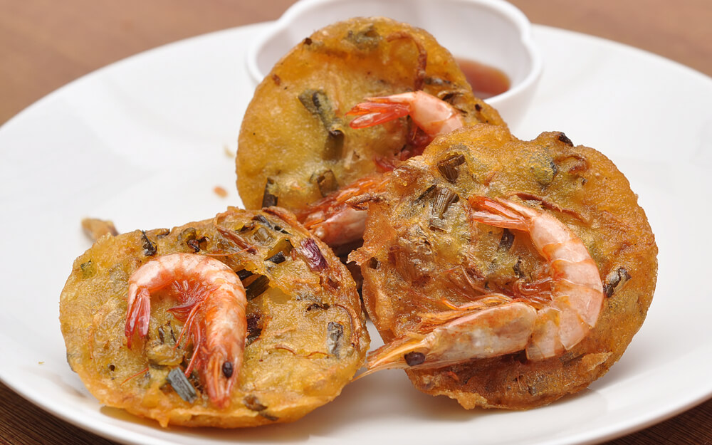 Cucur udang on a plate with chili dip