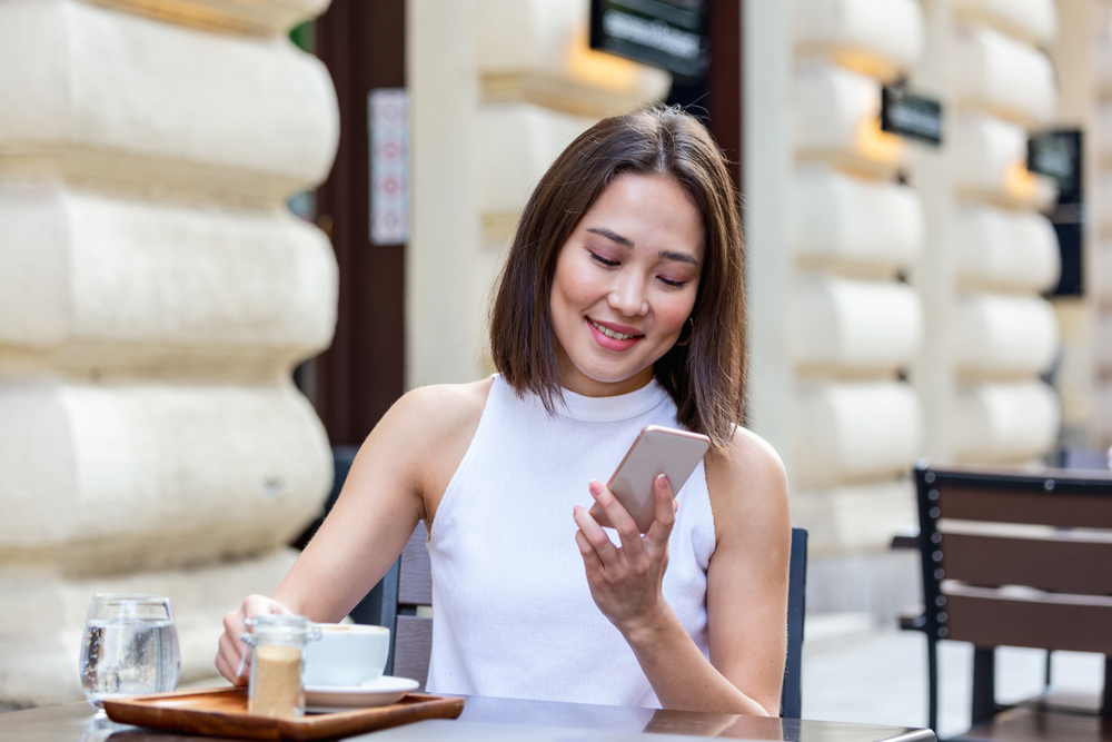 Smiling Asian woman drinking coffee and using her mobile phone while doing groceries shopping