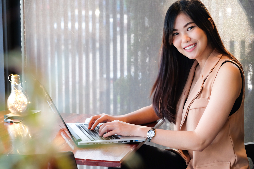 Smiling asian business women using laptop in modern coffee shop
