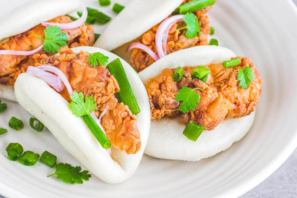 Grilled chicken Gua Bao stuffed with cilantro